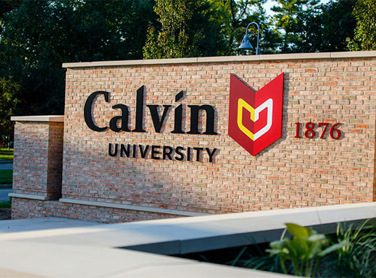 Calvin University logo displayed on red brick marquee on Calvin University campus